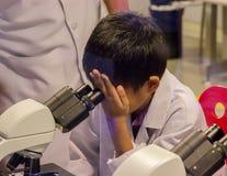 Asiatisk pojke som ser till och med mikroskopet arkivbild