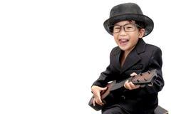 Asiatisk pojke som spelar gitarren på isolerad vit bakgrund arkivfoton