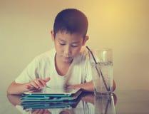 Asiatisk pojke som spelar tabellen på tabellen med den kalla drinken Royaltyfria Bilder