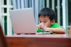 Asiatisk pojke som tycker om moderna utvecklingsteknologier som inomhus spelar Fotografering för Bildbyråer