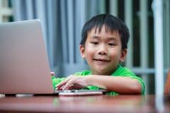 Asiatisk pojke som tycker om moderna utvecklingsteknologier som inomhus spelar Royaltyfri Bild
