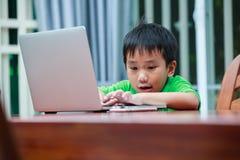 Asiatisk pojke som tycker om moderna utvecklingsteknologier som inomhus spelar Arkivbild