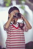 Asiatisk pojkefotograf med den yrkesmässiga digitala kameran i beaut Royaltyfri Fotografi