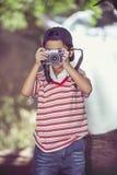 Asiatisk pojkefotograf med den yrkesmässiga digitala kameran i beaut Arkivfoto