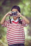 Asiatisk pojkefotograf med den yrkesmässiga digitala kameran på natur Royaltyfria Bilder