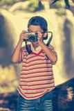 Asiatisk pojkefotograf med den yrkesmässiga digitala kameran på natur Royaltyfri Bild