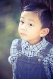 Asiatisk pojkelookingup utomhus Arkivfoto