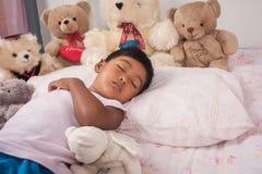 Asiatisk pojkesömn med nallebjörnen Arkivfoto