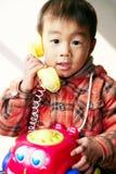 asiatisk pojkespelrumtelefon Royaltyfri Foto