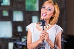 Asiatisk sångare producera sång i inspelningstudio Arkivfoto
