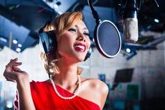 Asiatisk sångare producera sång i inspelningstudio Arkivbilder