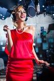 Asiatisk sångare producera sång i inspelningstudio Arkivbild