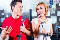 Asiatisk sångare producera sång i inspelningstudio Arkivfoton