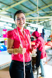 Asiatisk sömmerska i en textilfabrik Arkivfoto