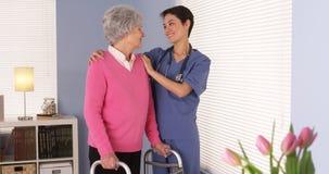 Asiatisk sjuksköterska och tålmodigt anseende för åldring vid fönstret Royaltyfri Foto