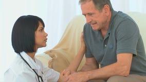 Asiatisk sjuksköterska som talar med hennes sjuka patient arkivfilmer