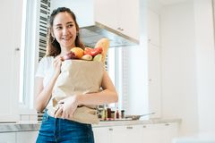 Asiatisk skönhetkvinna som alldeles rymmer av ingredienser för att laga mat aft fotografering för bildbyråer