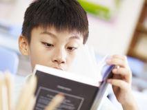 Asiatisk skolapojke som läser en bok Arkivfoto