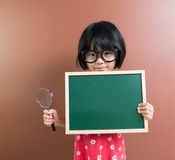 Asiatisk skolaungehåll en svart tavla och ett förstoringsglas Royaltyfri Fotografi