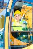Asiatisk skyffelgrävskopachaufför på konstruktionsplats Arkivfoton