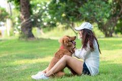 Asiatisk smilling livsstilkvinna som spelar och som är lycklig med golden retrieverkamratskaphunden i soluppgång royaltyfria foton