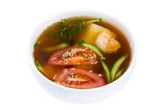 asiatisk soup Soppa i en platta som isoleras på vit bakgrund Havs- soppa med räkor, tomater och tofuost royaltyfria bilder