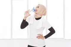 Asiatisk sportig kvinna som dricker mineralvatten efter genomkörare Royaltyfri Fotografi