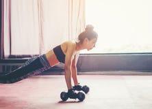 Asiatisk sportkvinna som gör övningar med hanteln och push-UPS på royaltyfri foto