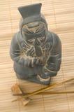 Asiatisk statyett och två pinnar Royaltyfri Foto