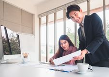 Asiatisk stilig affärsman att förklara jobbdetaljer till den härliga affärskvinnan royaltyfria foton