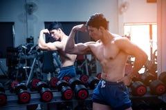 Asiatisk stilig ung muskulös asiatisk man som framme övar kroppsbyggaren av ett exponeringsglas i idrottshallen Grabb som böje royaltyfri foto