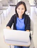 Asiatisk student som använder bärbara datorn arkivfoton
