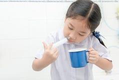 Asiatisk studentflicka som spolar hennes näsa med injektionssprutan och saltdam Arkivfoto