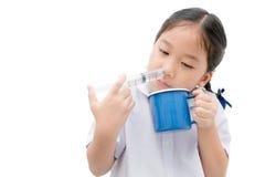 Asiatisk studentflicka som spolar hennes näsa med injektionssprutan och saltdamiso Royaltyfria Bilder