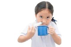 Asiatisk studentflicka som spolar hennes näsa med injektionssprutan och saltdamiso Royaltyfri Bild
