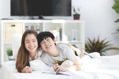 Asiatisk syster och broder som kopplar av och spelar på thersäng fotografering för bildbyråer
