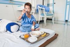 Asiatisk tålmodig pojke med salthaltigt intravenöst (iv) på sjukhussäng. arkivfoton