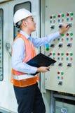 Asiatisk tekniker på panelen på konstruktionsplats Arkivbild