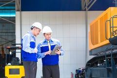Asiatisk tekniker som diskuterar plan på konstruktionsplats Royaltyfria Foton