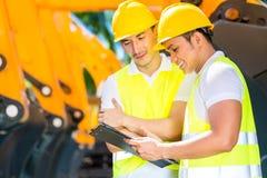 Asiatisk tekniker som diskuterar plan på konstruktionsplats Royaltyfri Foto
