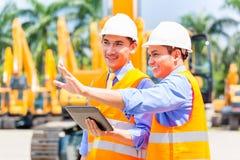 Asiatisk tekniker som diskuterar plan på konstruktionsplats Royaltyfri Fotografi