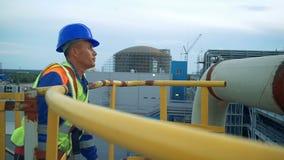 Asiatisk tekniker som klättrar tornet av ett stort oljeraffinaderi stock video