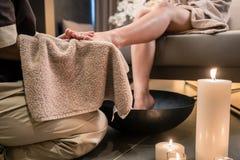 Asiatisk terapeut som torkar foten av en kvinnlig klient efter terapeutisk tvagning arkivbild