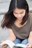 Asiatisk tonårig det kvinnaläseboklycka och leendet tycker om utbildning arkivfoton