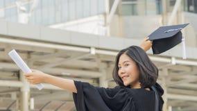 Asiatisk tonårig flicka med avläggande av examenkappatorkduken med mening lyckligt royaltyfri bild