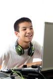 Asiatisk tonåring som använder datoren med den smily framsidan Arkivfoto