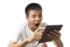 Asiatisk tonåring som använder hans minnestavla och gäspning Arkivfoto