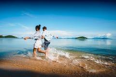 Asiatisk tonårs- flicka- och pojkespring på stranden arkivbild