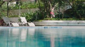 Asiatisk tonårs- pojke som hoppar upp och ner faller in i den utomhus- simbassängen Royaltyfri Bild