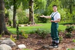 Asiatisk trädgårdsmästare som framlägger den härliga trädgården Royaltyfri Fotografi